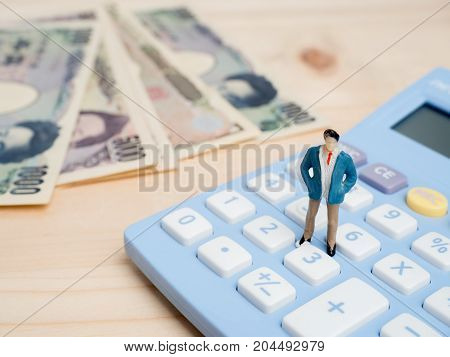 Business Concept. businessman small figures standing on calculator.