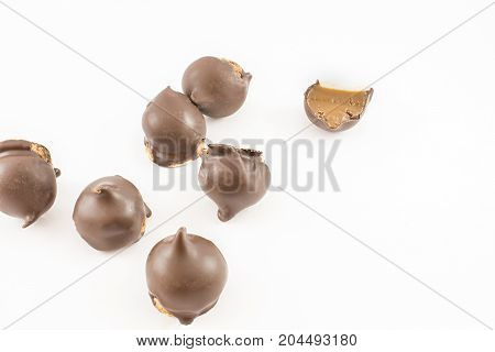 Many cones of dulce de leche and chocolate whole and cut in half. White background.