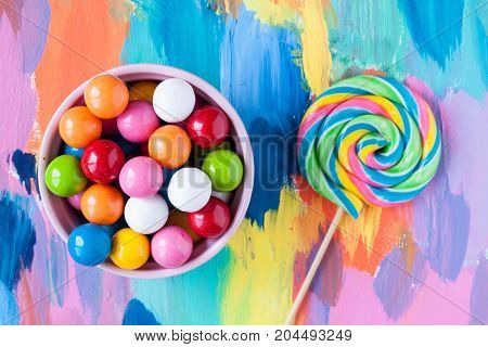 bubble gummy candies and lolliop on a colorful background