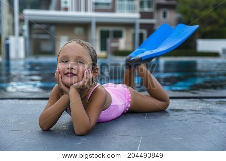A happy young girl relaxing on the side of a swimming pool wearing Flippers