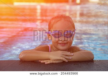 A happy young girl relaxing on the side of a swimming pool wearing goggles. Toned