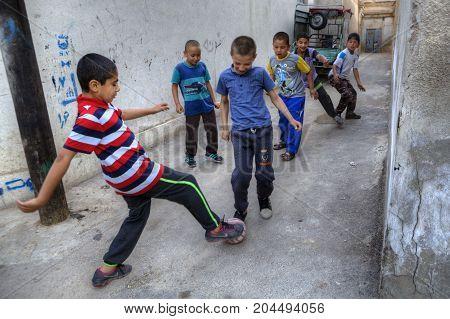 Fars Province Shiraz Iran - 18 april 2017: Iranian teenagers playing football in a courtyard.