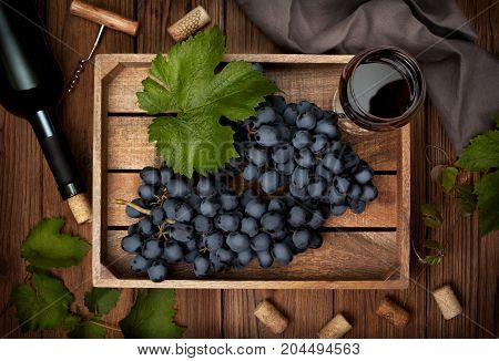 wooden box with grapes and a glass of wine a bottle of wine on the old wooden background. view from above