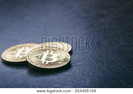 Golden bitcoin coins on a dark background with reflection. Virtual currency. Crypto currency. New virtual money. Lens flare