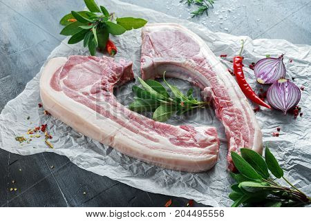 Fresh Pork middle cut ready to cook served with sage, red onion, chillies and red pepper drizzled with olive oil on roasting paper.