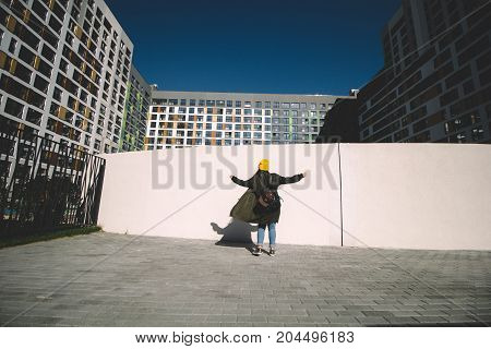 Girl Hipster Dancing Against White Wall  In The Urban Area Of A Big City