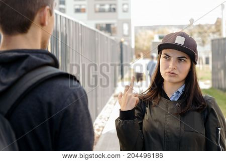A Young Girl In The Cap Shows The Middle Finger (fuck You Sign) With My Boyfriend( Man's Back)