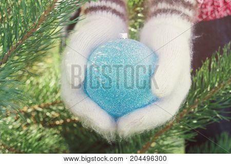 Girl Hands In Woollen Mittens Holding Christmas Blue Ball