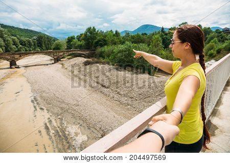 Young girl traveler leads man by hand and shows by other hand at ancient bridge, follow me concept