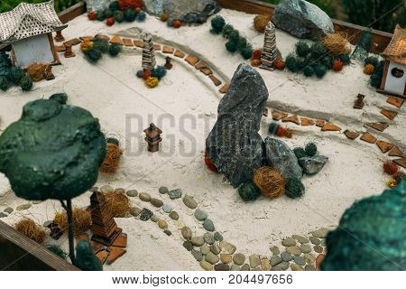Miniature houses, toy landscape objects on the sand. Sand therapy. Toy landscape layout on sand from toy items
