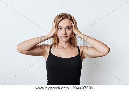 Waist Up Portrait Of Pretty Girl Has Headache After Noisy Party, Keeps Hands On Head, Poses Against