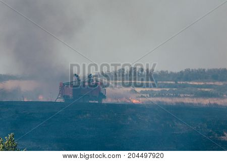 The fire truck and rescuers extinguish forest fires and fires in the fields, a lot of smoke from the fire