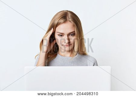 Concentrated Female Freelancer Works At Laptop Computer, Translates Article While Sits At Her Workpl