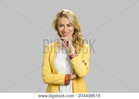Portrait of smiling business woman. Cheerful young lady holding chin on hand and smiling against grey background. Smiling beautiful young executive.