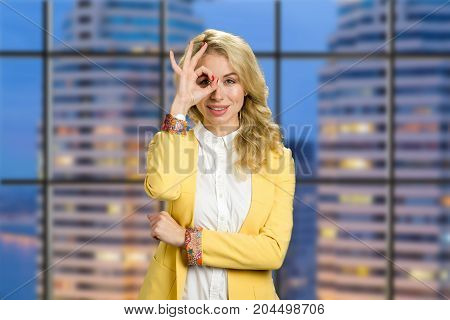 Beautiful woman on evening skyscraper background. Attractive business lady in yellow jacket and white shirt gesturing ok on evening business center background.