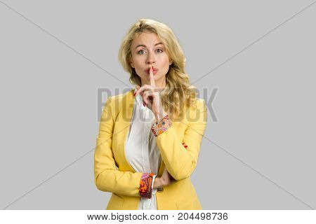 Pretty girl making silence gesture. Confident young woman placing finger on lips gesturing silence standing on grey background.