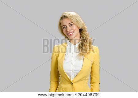 Portrait of smiling young business woman. Blond lady in yellow jacket and white shirt smiling on grey background.