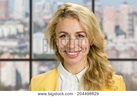 Detail of smiling young woman. Close up portrait of attractive blod girl smiling on office widow background.