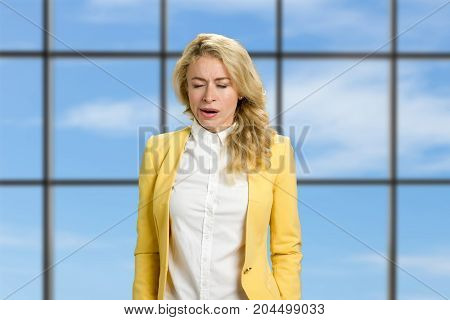 Young business woman yawning in office. Beautiful young woman yawning with closed eyes against blue sky office window background. Awaking after night dream.