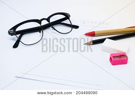 Black glasses white paper pencil pen pink sharpener and eraser (rubber) for write your note - concept relax.