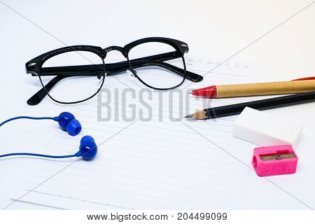 Black glasses white paper pencil pen pink sharpener eraser (rubber) and blue earphone for write your note - concept relax.