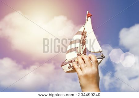 Hand of kid holding a hand made ship on the sky