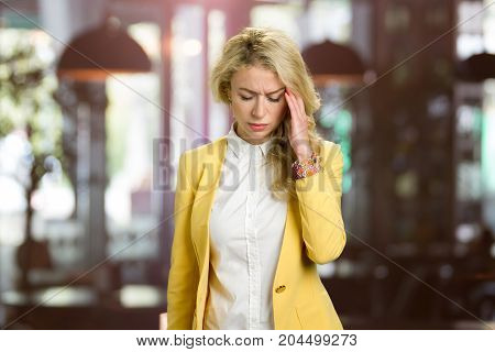 Beautiful woman having migraine. Tired exhausted stressed woman suffering from strong headache, blurred background.