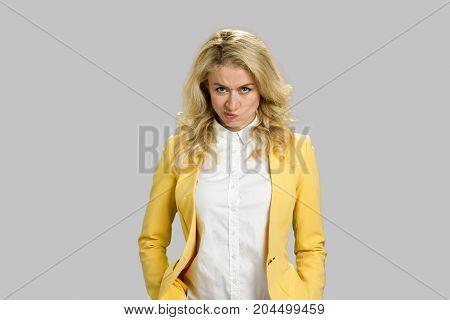 Displeased young woman, grey background. Pretty young annoyed woman standing isolated on grey background. Human facial expressions.