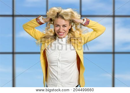 Smiling woman holding hands in hair. Shot of lovely long blond hair girl in yellow jacket posing on office window background at the camera.