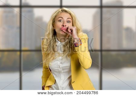 Young woman making funny lips. Young business woman making funny grimace with her lips standing on business center window background.