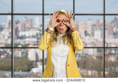Young business woman making binoculars hands. Young cheerful woman having fun and making binoculars using her hands standing on office window background.