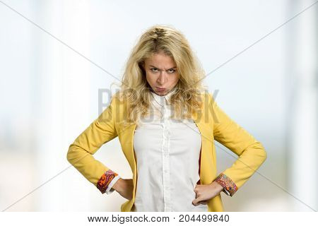 Young blonde standing with hands on hips. Angry young business woman keeping hands on waist.