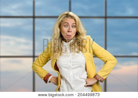 Beautiful young woman making surprised grimace. Young white-skin woman making funny astonished face with wide open eyes and hands on hips, office window background.