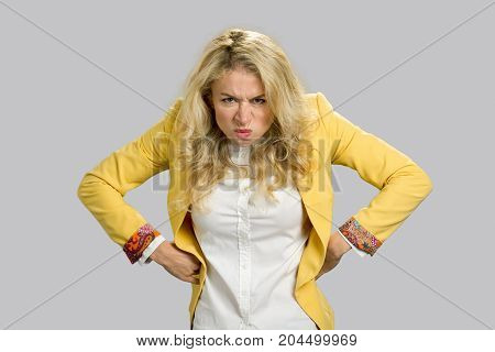 Aggressive frowning young business woman. Frustrated european woman in formal wear holding hands on hips with negative emotions and facial expressions, grey background.