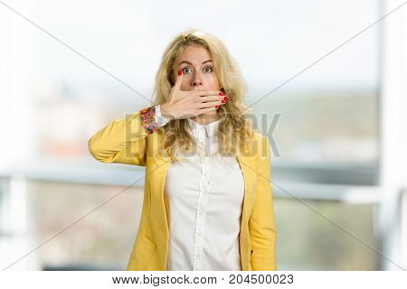 Shocked woman covering her mouth. Beautiful scared blonde business woman covering her mouth with hands palm, blurred background.