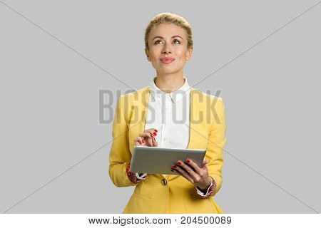 Portrait of positive thoughtful female manager. Pretty young woman in formal wear looking thinking while holding pc tablet, grey background.
