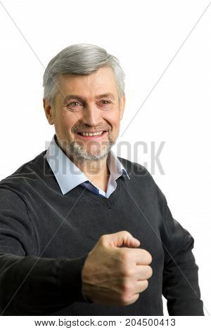 Smiling mature man clasped fist. Grey haired man clenching his fist with positive smile on white background.