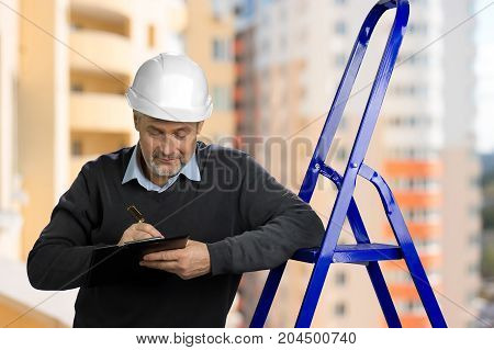 Portrait of mature building inspector. Senior engineer leaning on ladder and writing on clipboard, blurred background.