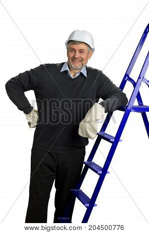 Happy mature foreman, white background. Handsome senior engineer standing and leaning on building ladder. Building inspector looking on building process.