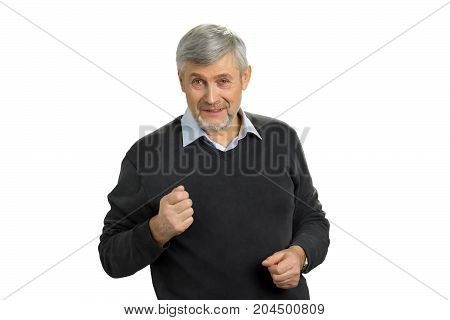 Angry mature man on white background. Portrait of senior man showing fist. Irritated mature man putting his fist up. Facial expressions, emotions and interpersonal conflict resolution.