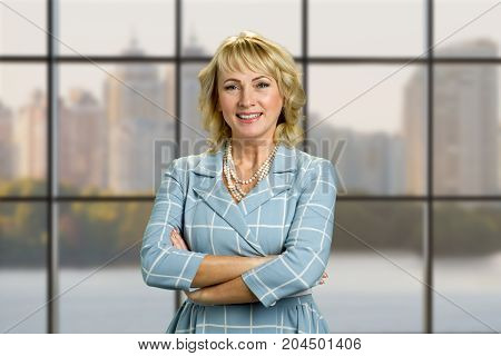 Mature woman with crossed arms portrait. Smiling businesswoman with crossed arms on office window background.