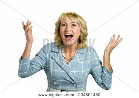 Excited mature woman raised hands. Adult woman opens mouth with great excitement and raised her hands on white background.