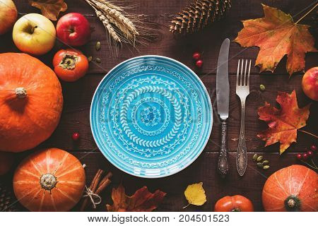 Autumn Halloween or thanksgiving day table setting. Fallen leaves, pumpkins, spices, empty plate and vintage cutlery on wooden table. Top view, toned image