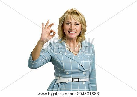 Elegant mature woman showing ok sign. Attractive mature lady showing ok sign isolated over white.