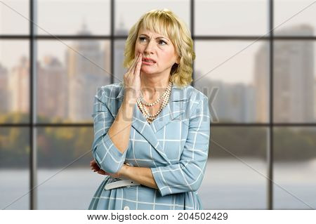 Mature woman feeling toothache. Beautiful sad middle aged woman suffering from strong tooth pain while standing on office window background.