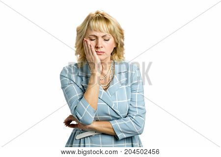 Middle aged woman suffering from toothache. Attractive sad mature woman suffering from strong tooth pain closed eyes and touching cheek standing on white background.