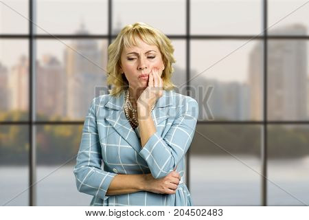 Unhappy mature woman suffering toothache. Beautiful middle aged woman suffering from terrible strong teeth pain, touching cheek standing on office window background. Tooth pain and dentistry.