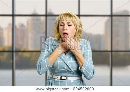 Mature woman suffering from couging. Middle aged blonde is coughing on office window background.