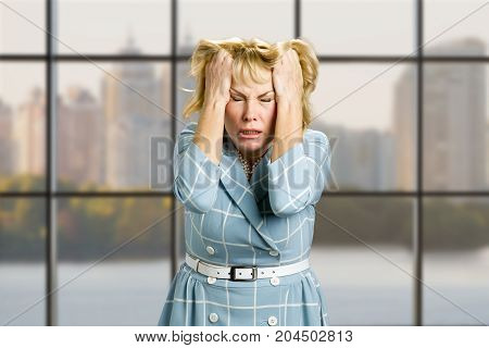 Mature woman in full desperation. Depressed business woman with closed eyes pulling her hair on office window background.
