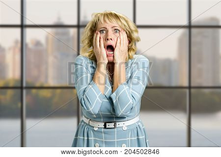 Shocked and frustrated mature woman. Middleaged woman looking shocked in full desperation and disbelief on office window background.